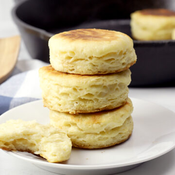 Biscuits stacked on a white plate.
