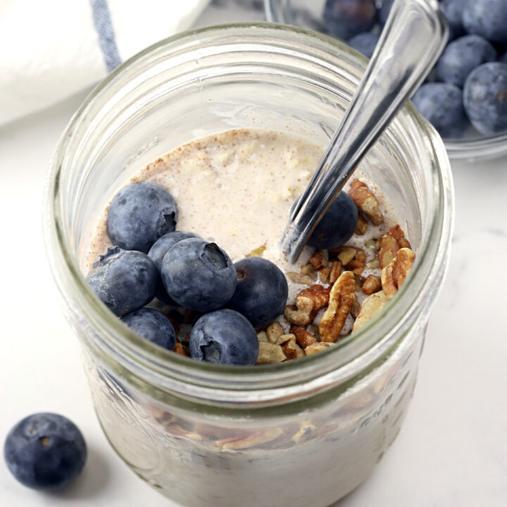 Overnight oats in a jar with blueberries and a spoon.