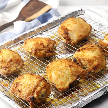 Crispy baked chicken thighs on a baking sheet.
