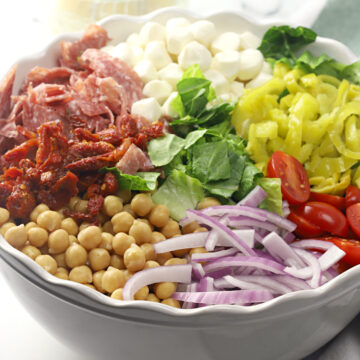 Ingredients on top of a bed of lettuce in a bowl.