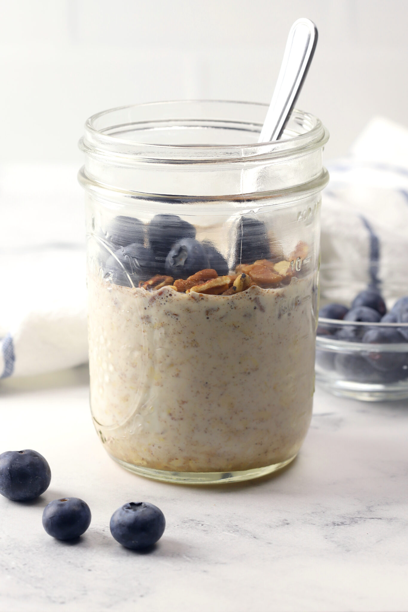 Jar of overnight oats topped with pecans and blueberries.