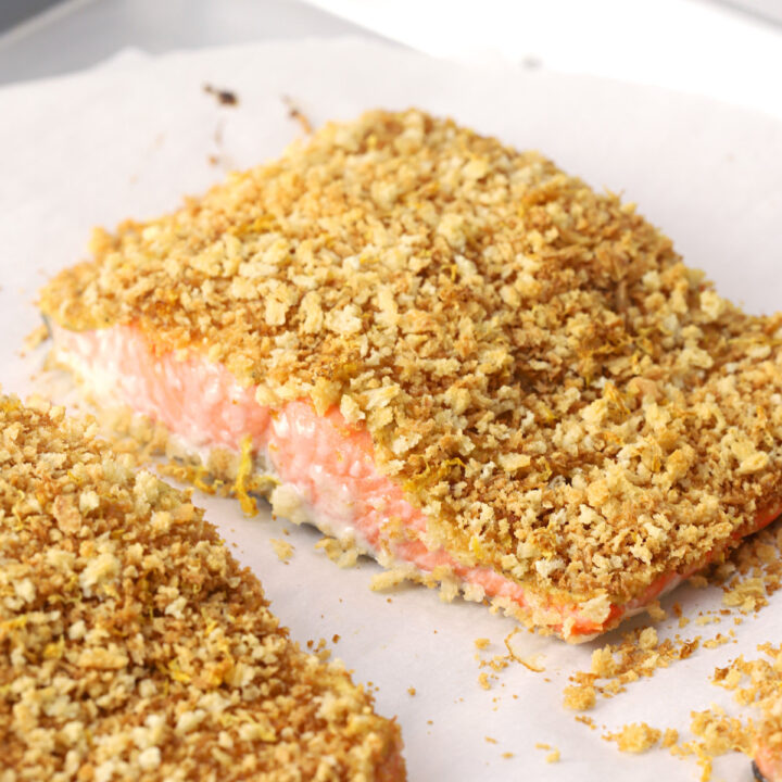 Pieces of panko crusted salmon on a metal sheet pan.