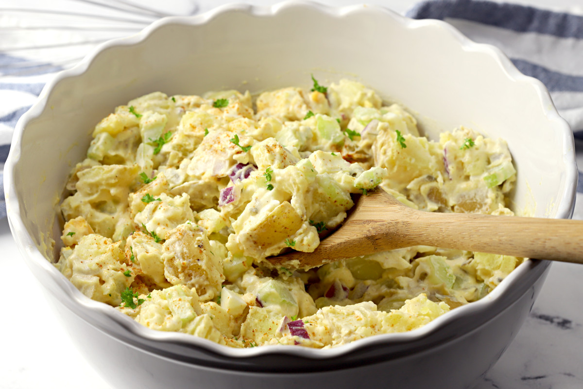Potato salad in a scalloped bowl with a spoon.