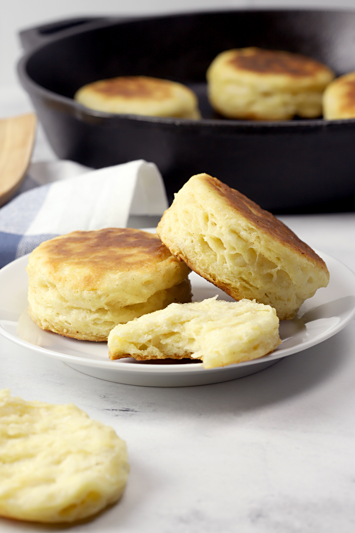 Biscuits on a plate with skillet in the background.