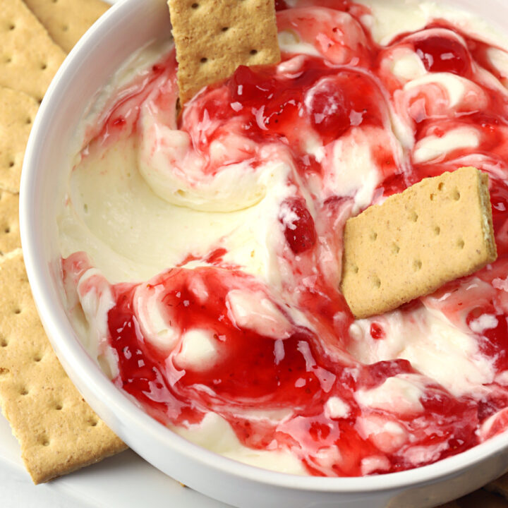 Graham crackers dipped in a bowl of strawberry cheesecake dip.
