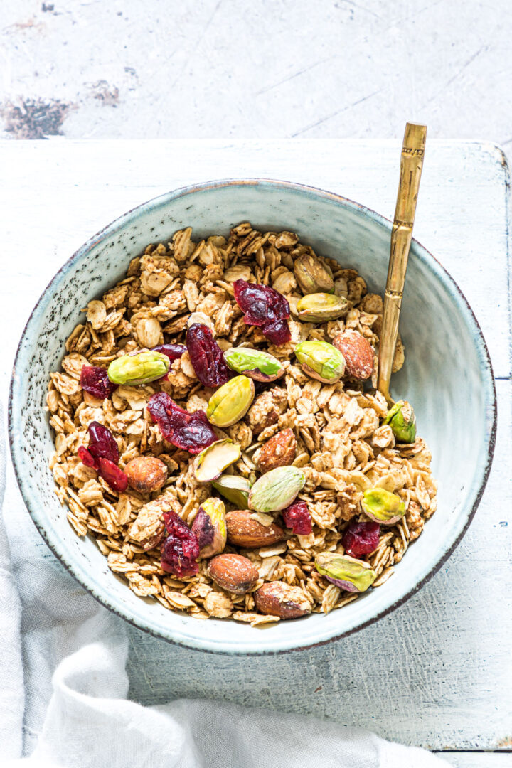 A bowl filled with granola topped with cranberries and pistachios.