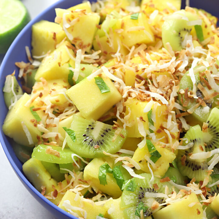 A blue bowl filled with pineapple and kiwi.