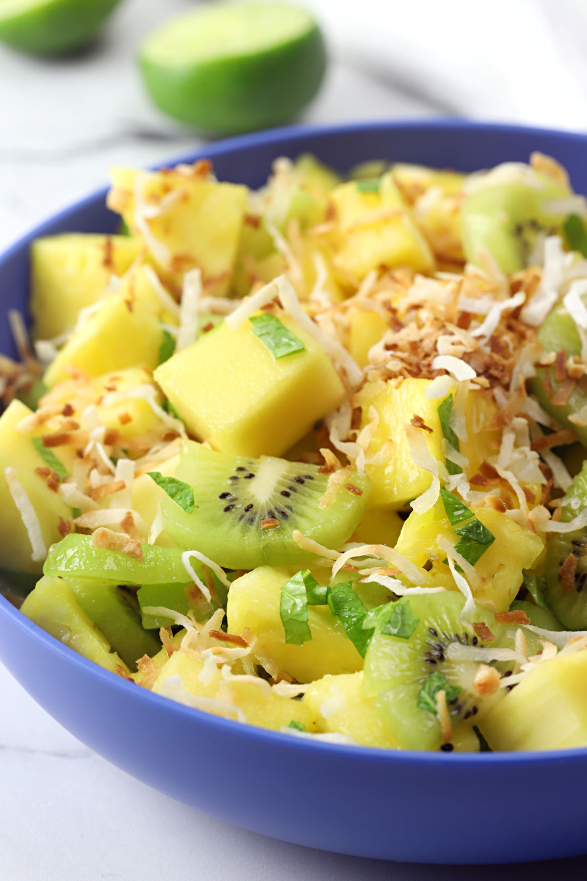 Pineapple kiwi salad in a blue bowl topped with toasted coconut.