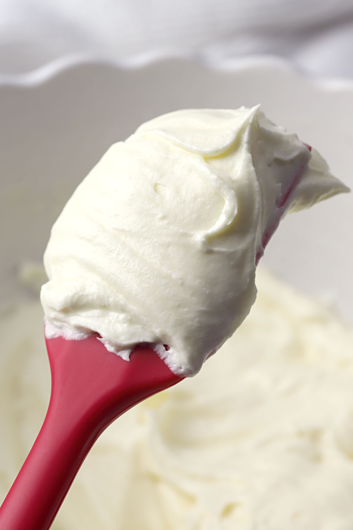 Red spatula covered in white frosting.