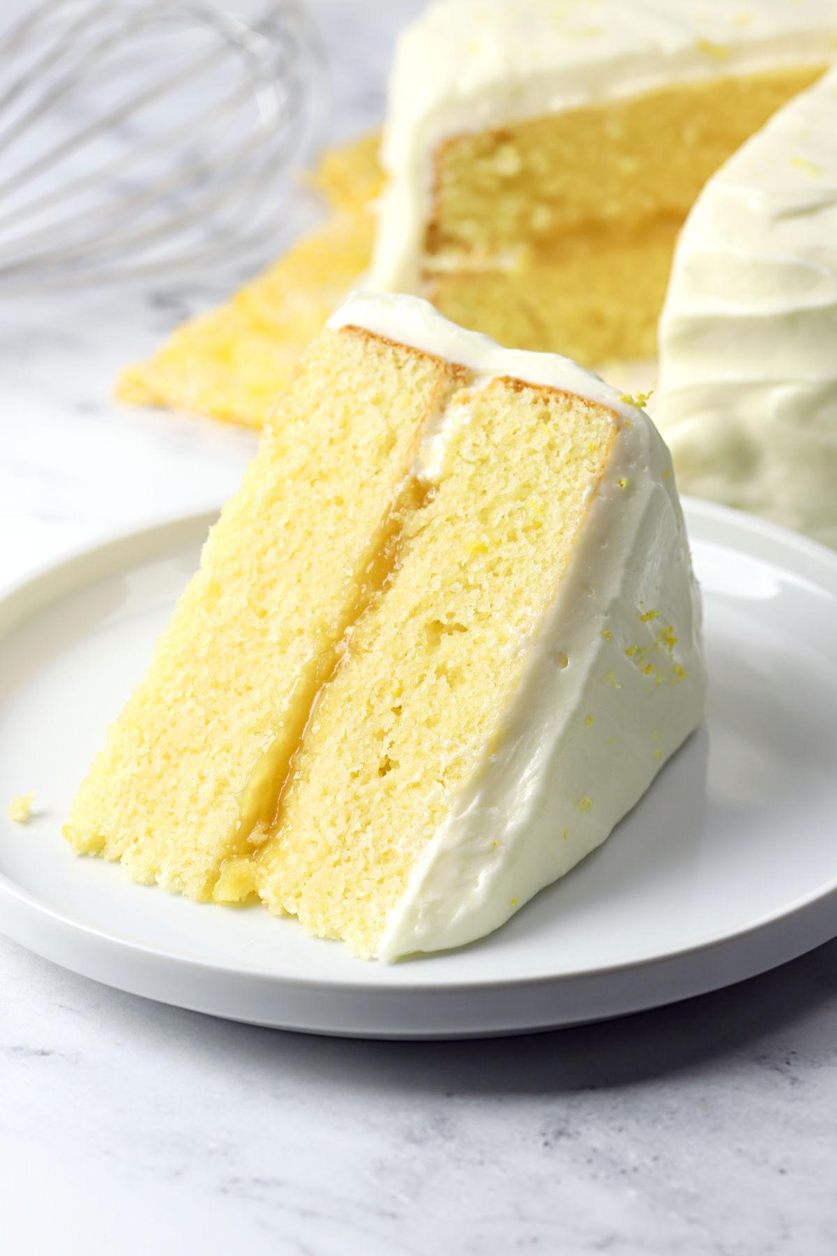 Slice of lemon layer cake on a white plate.
