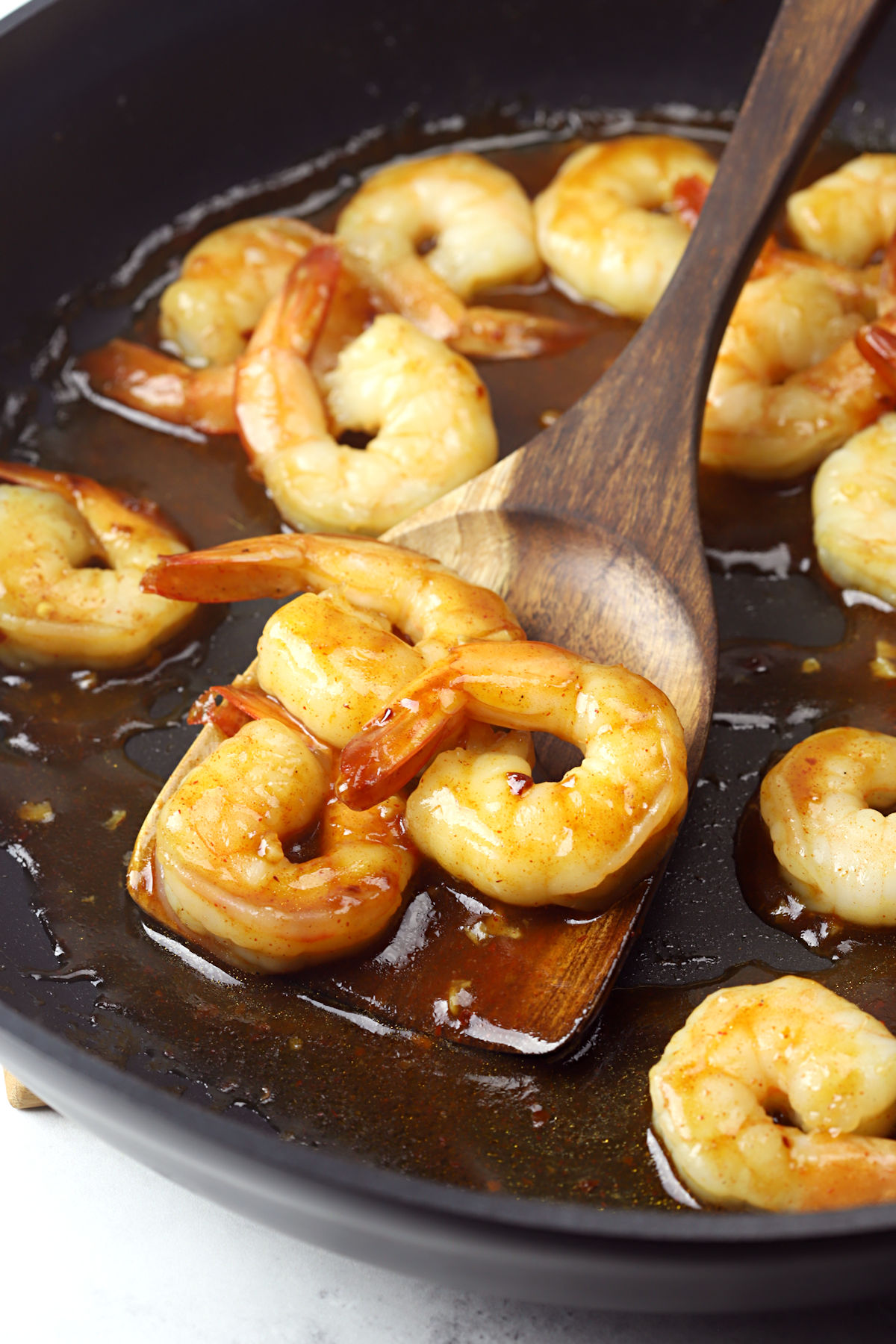 Wooden spatula scooping shrimp from a skillet.