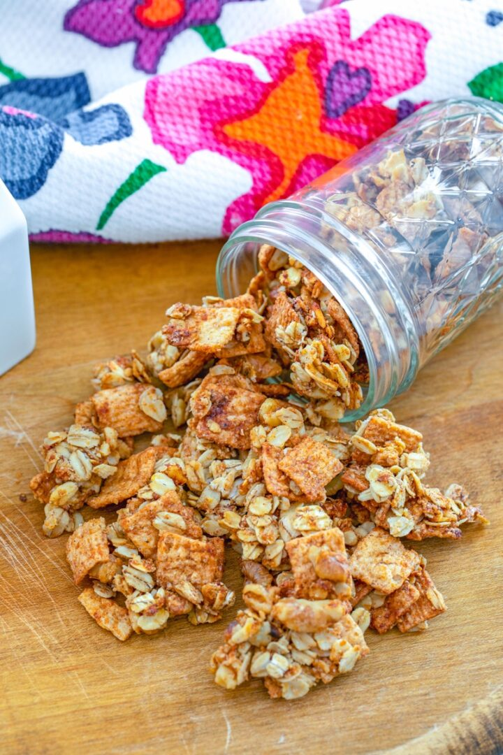 A jar of granola spilling onto a wooden cutting board with a floral kitchen towel.