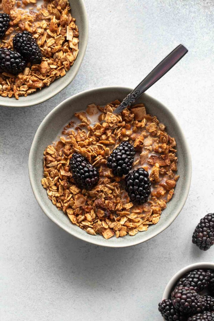 Maple granola in a bowl with a spoon, topped with blackberries.