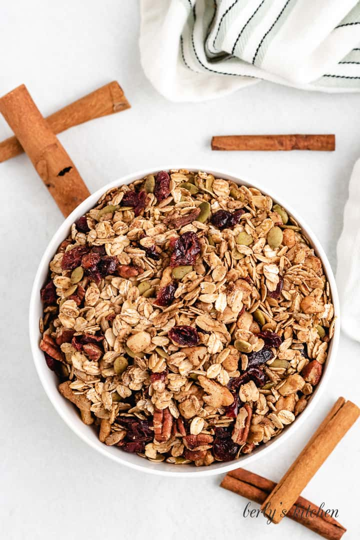 White bowl filled with granola, sitting with cinnamon sticks on a counter top.