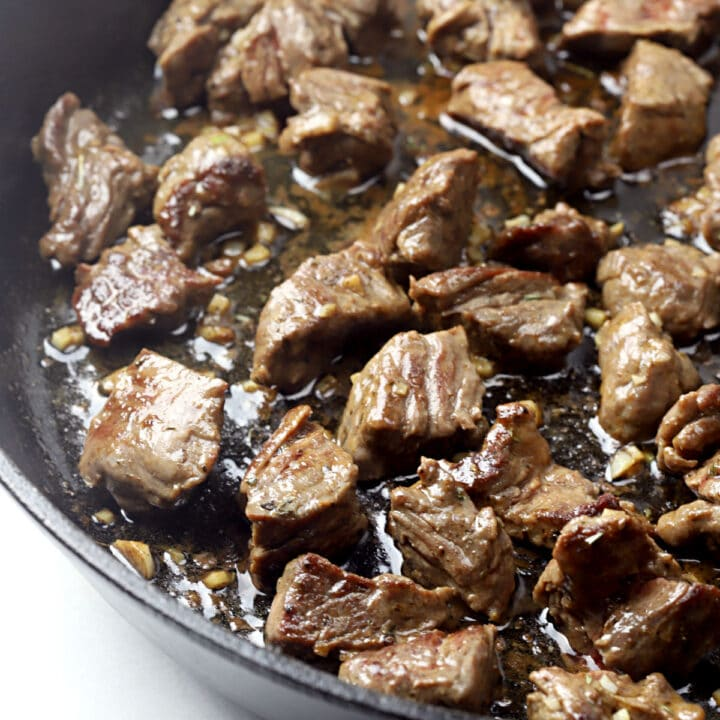 Cooked steak tips in a cast iron pan.