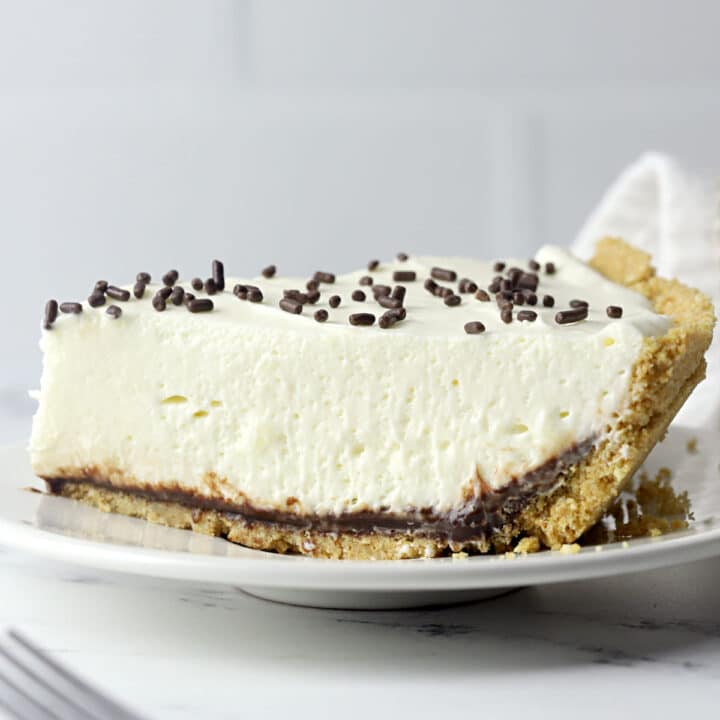 Side view of a slice of marshmallow pie topped with chocolate sprinkles on a small plate.