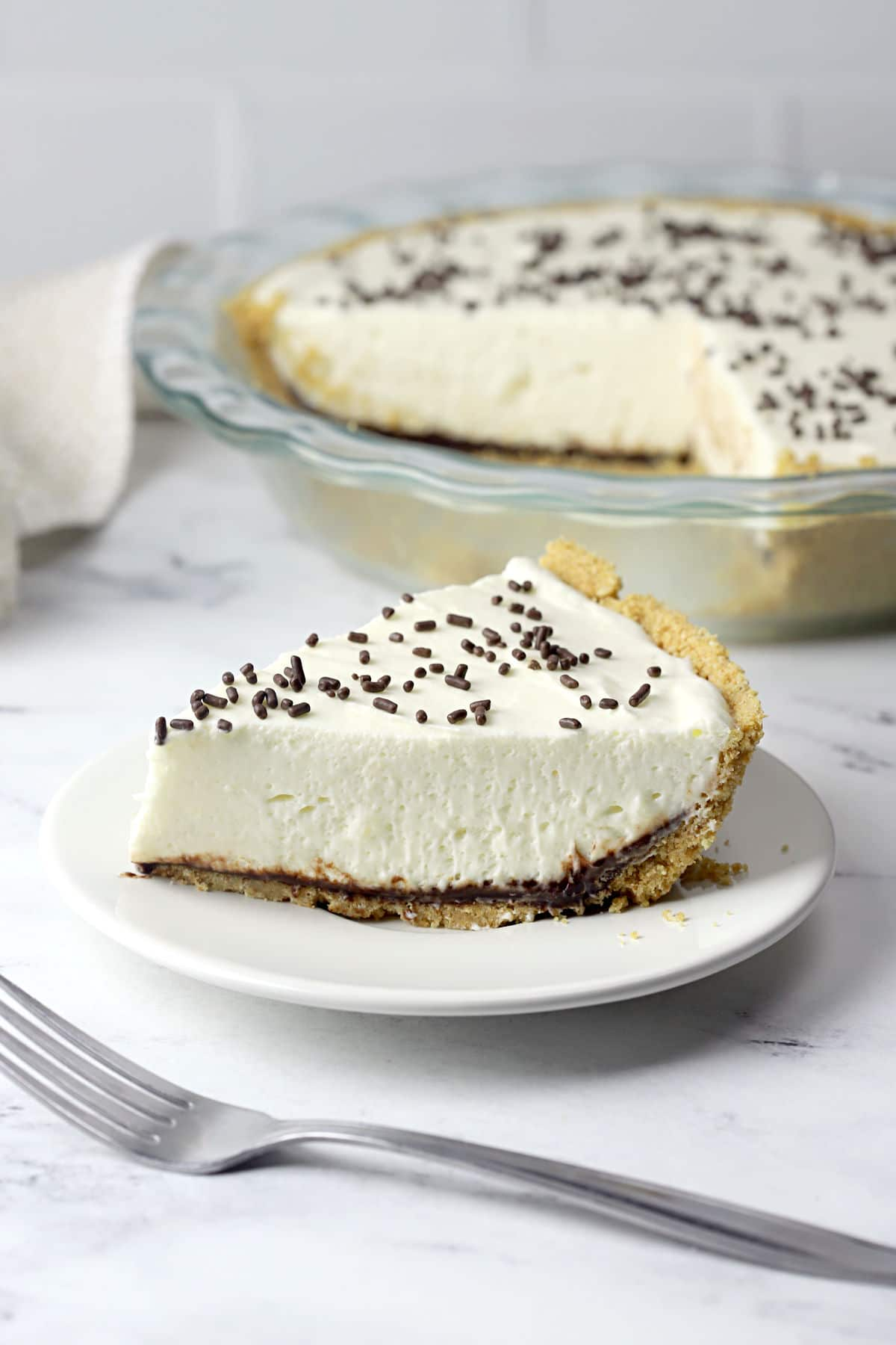 A slice of pie with layers of hot fudge and white marshmallow filling, with a sliced pie sitting in the background.