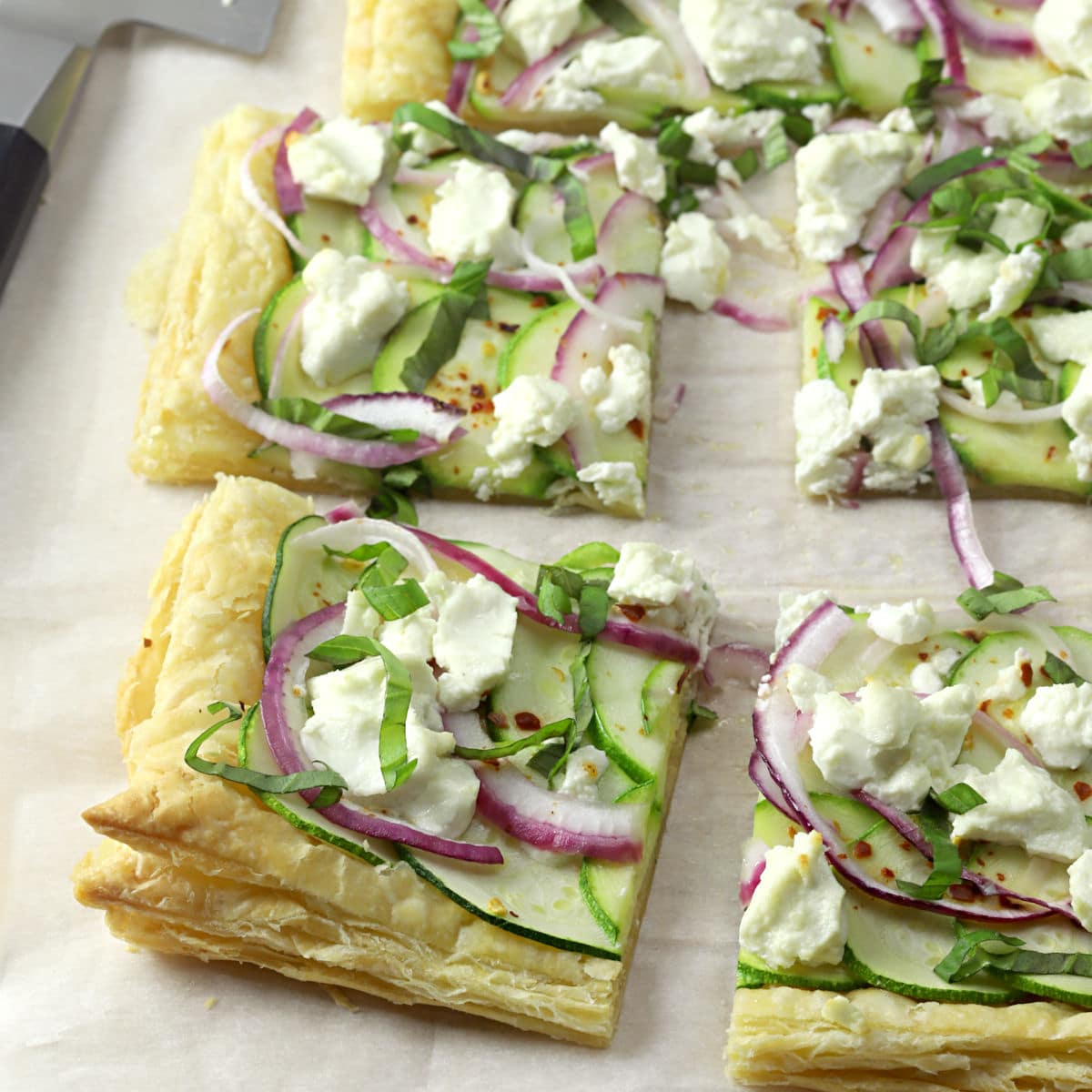 A puff pastry tart sliced into squares on a sheet of parchment paper.