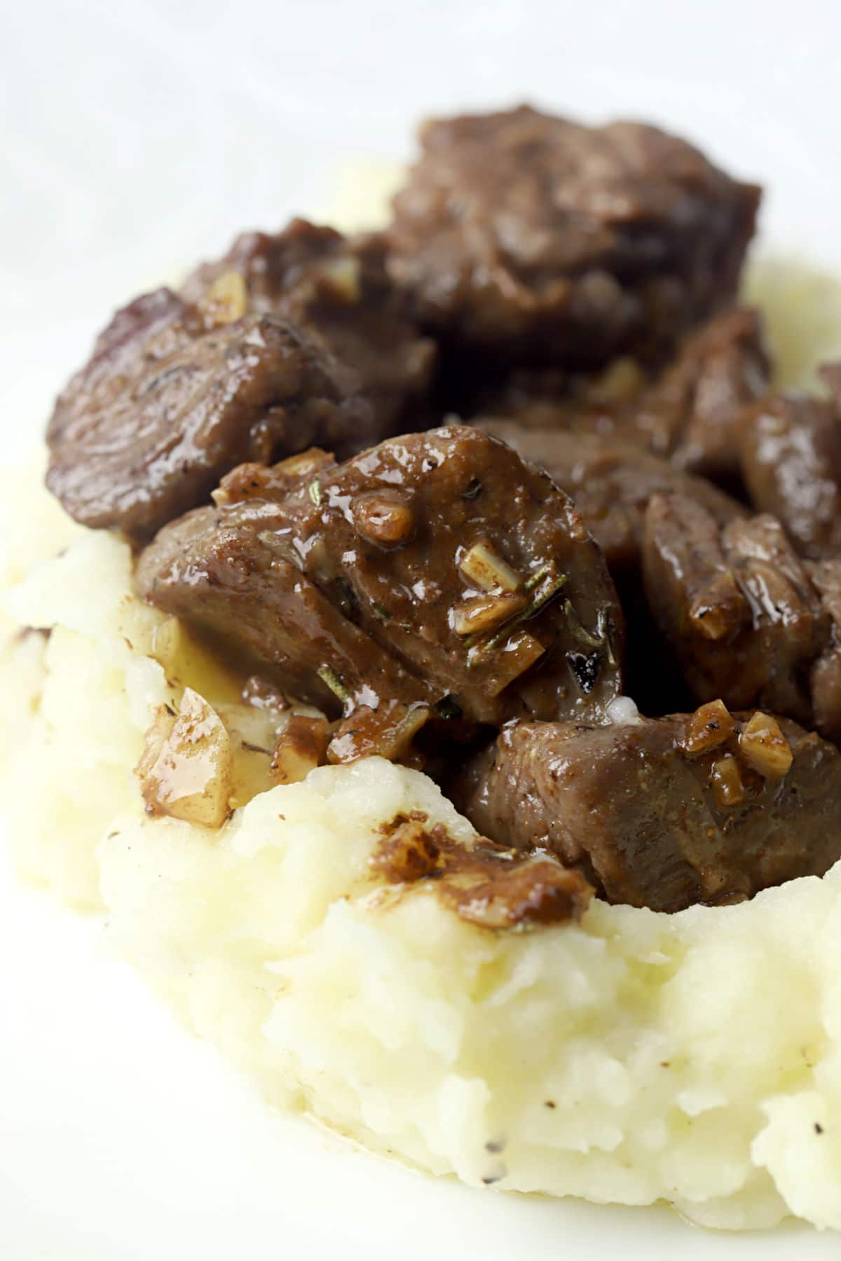 Sirloin tips sitting on a bed of mashed potatoes.