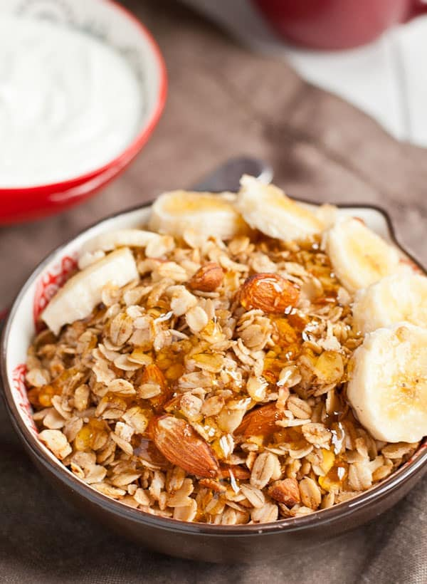 Granola in a bowl topped with sliced bananas and honey.