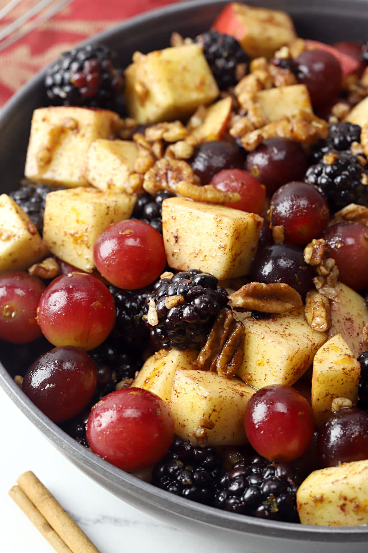 Close up of grapes, cubed apple, and blackberries coated in a cinnamon dressing in a bowl.