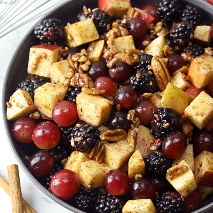 A bowl filled with fruit salad next a red and gold kitchen towel and cinnamon sticks.