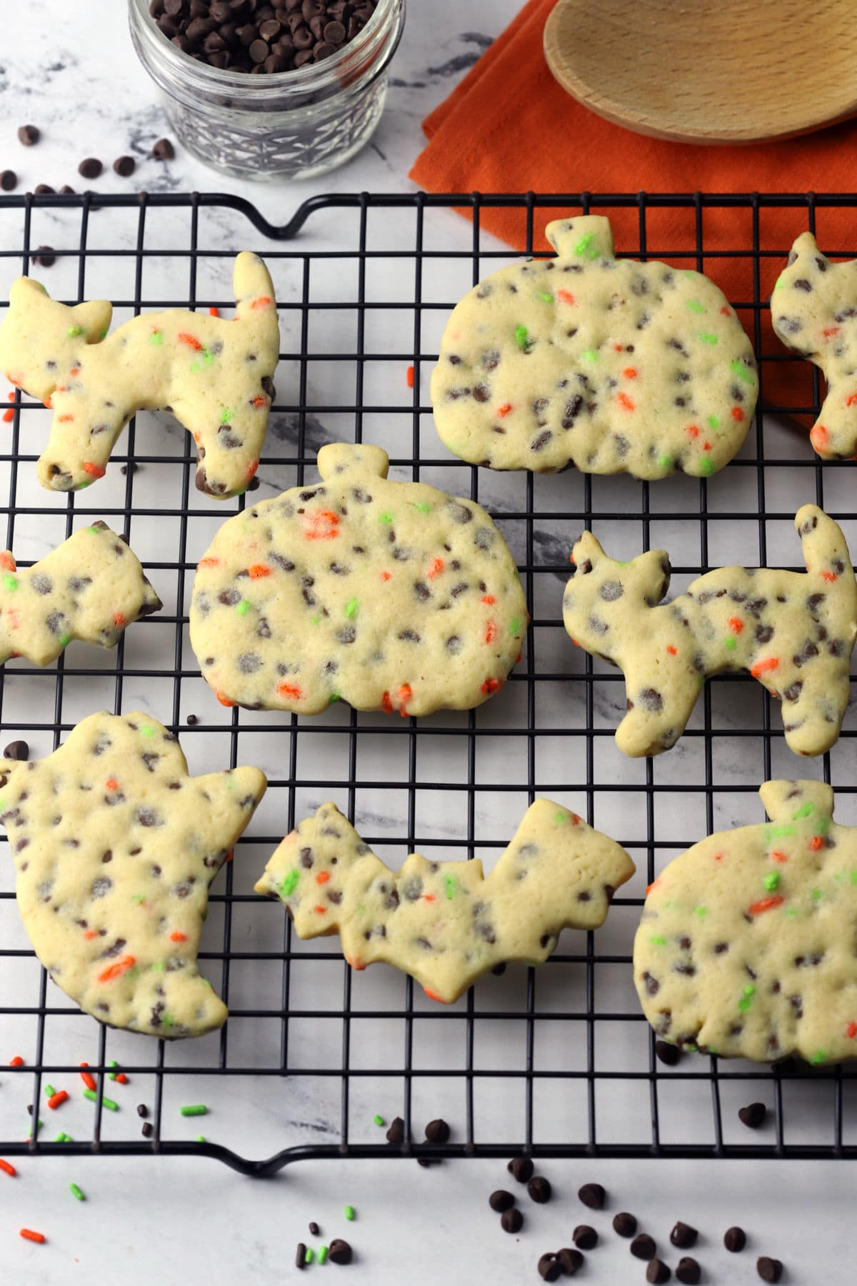Halloween shaped cut out cookies on a cooling rack.
