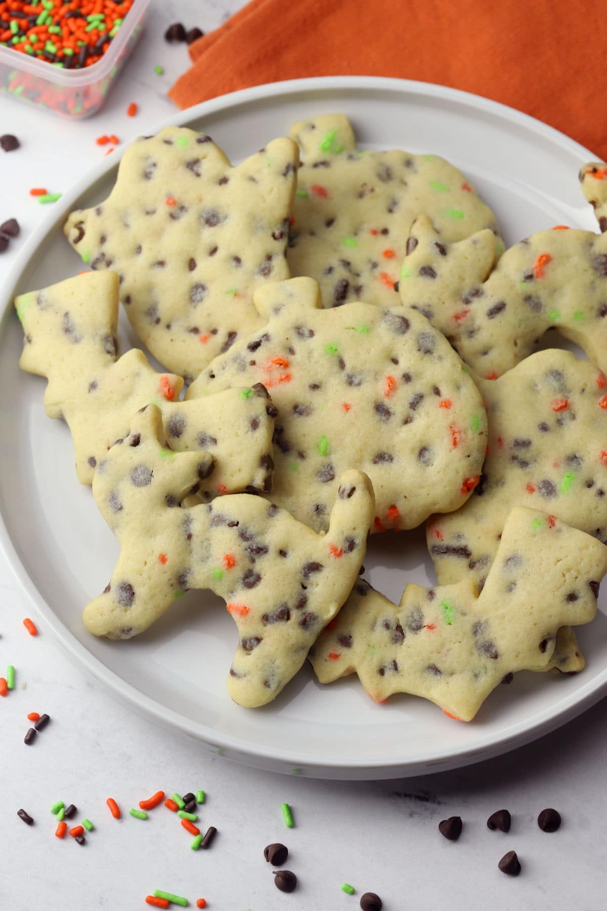 A white plate filled with chocolate chip cut out cookies shaped like cats, pumpkins, and bats.