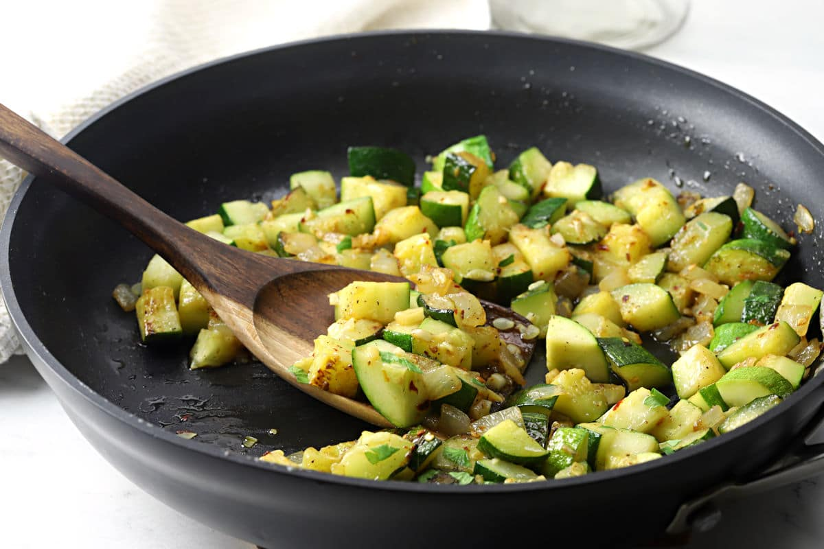 Wooden server scooping zucchini and onions from a skillet.