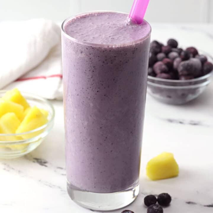 A glass filled with blueberry pineapple smoothie on a marble counter top.