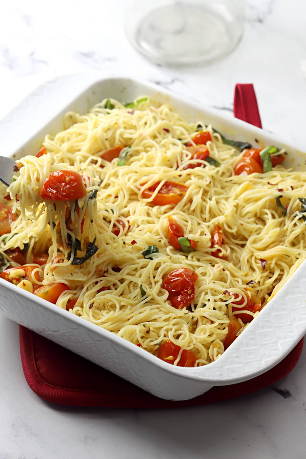 A white casserole dish filled with roasted cherry tomato pasta.