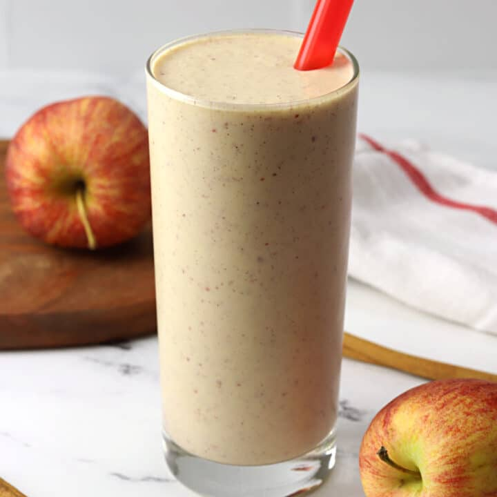 A glass filled with apple pie smoothie and a red straw.