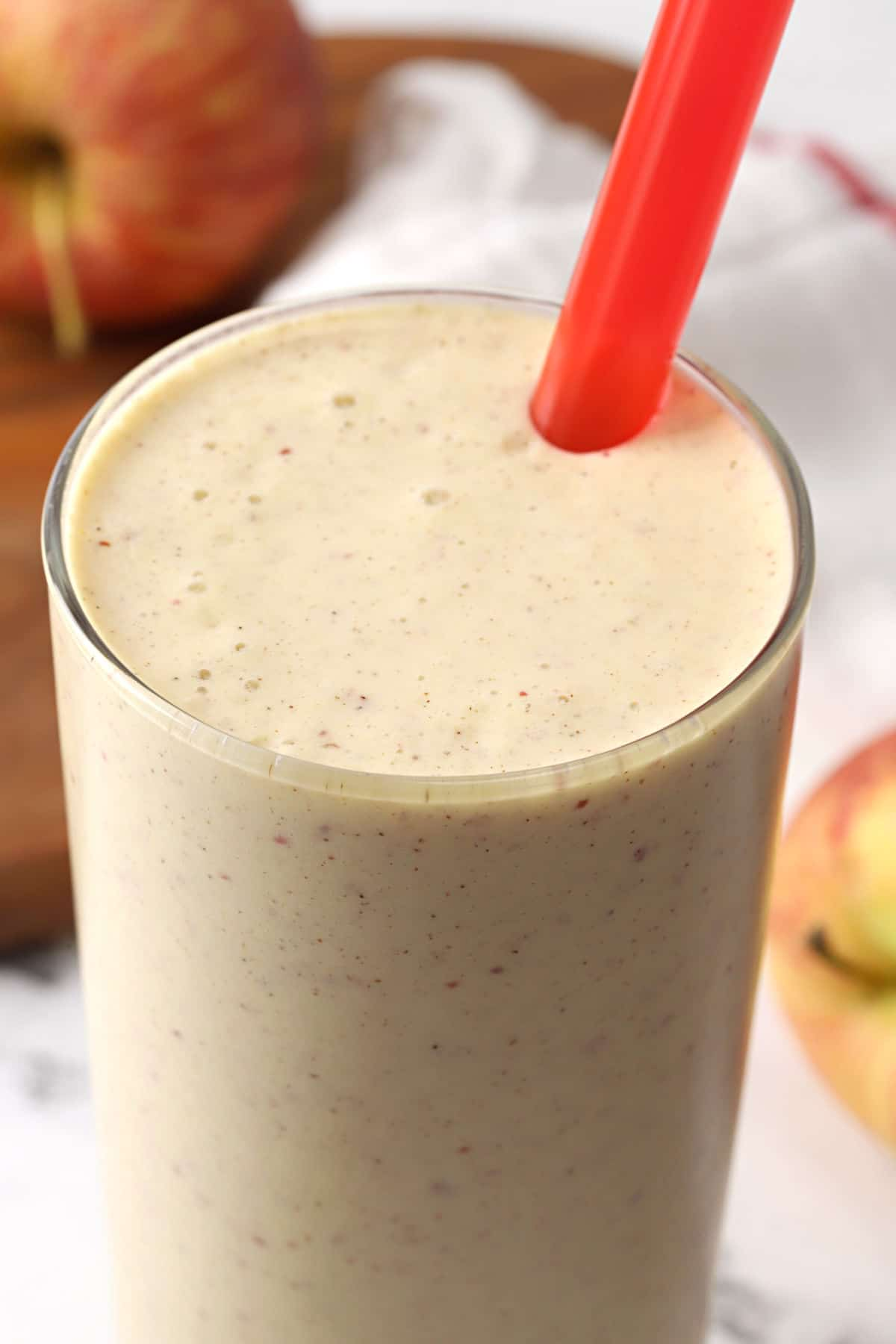 Close up of light brown smoothie in a glass with a red straw.