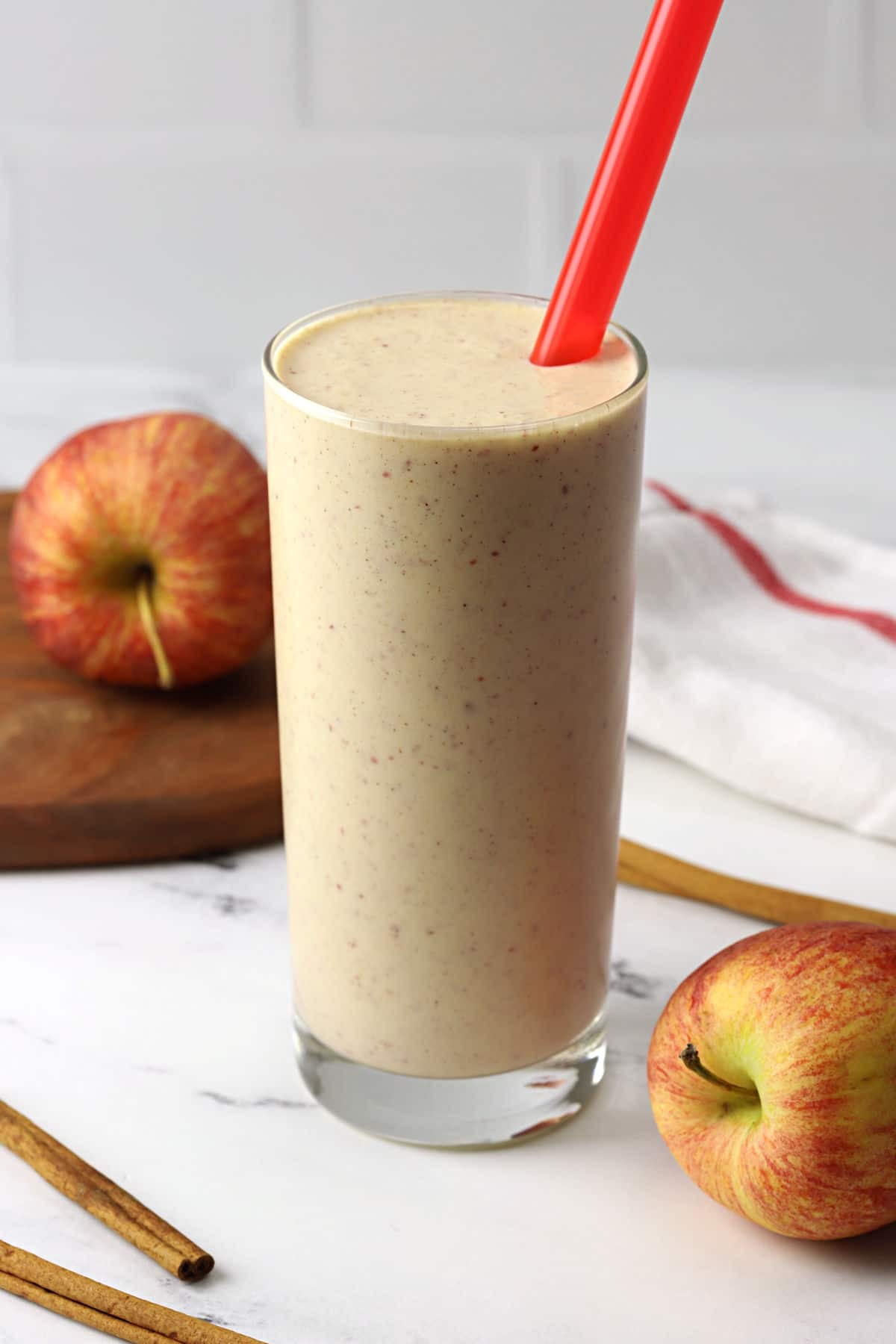 A tall glass filled with apple smoothie and a red straw.