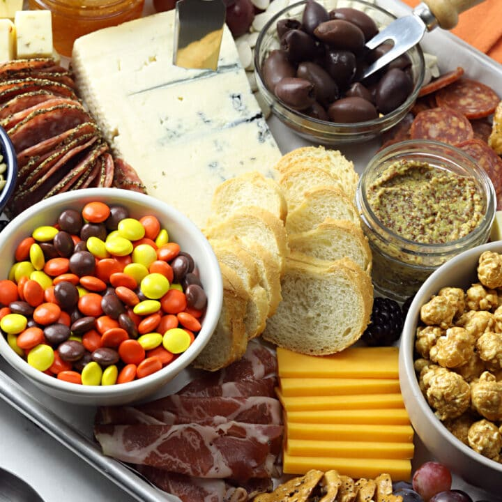 Close up of meats, cheeses, crackers, caramel corn, and candies on a Halloween charcuterie board.