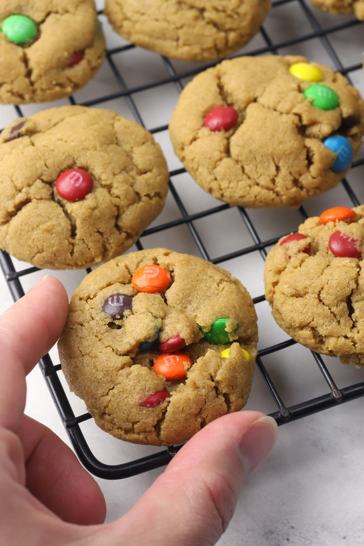 A hand reaching for a peanut butter cookie on a cooling rack.