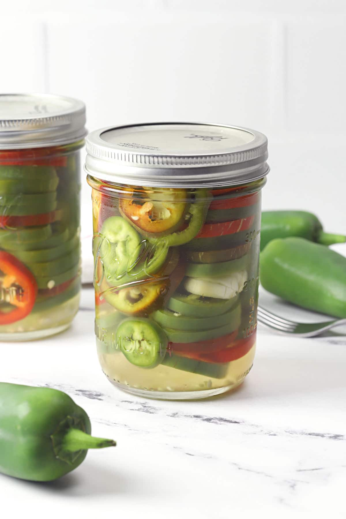 A jar of pickled jalapenos on a marble counter top.