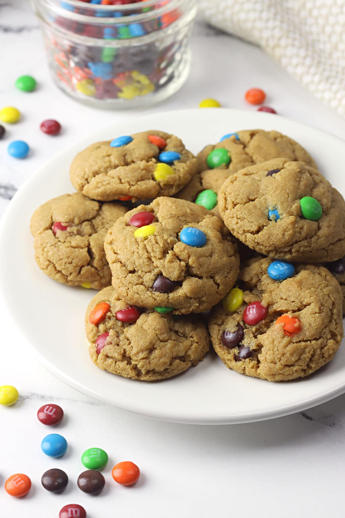 A white plate filled with small peanut butter cookies filled with colorful candies.