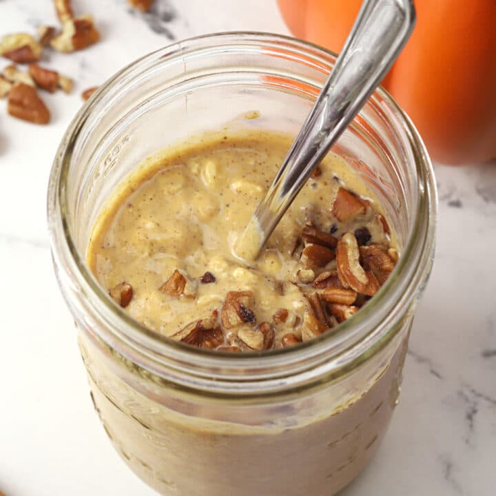 Glass jar of overnight oats topped with chopped pecans.