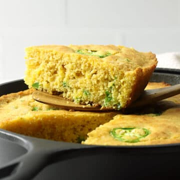 A wedge of jalapeno cornbread sitting on top of a cast iron pan.